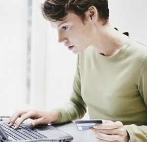 Woman Sits at a Desk Using a Laptop and Paying a Bill Online With Her Credit Card