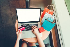 Woman with laptop shopping online with debit card in cafe